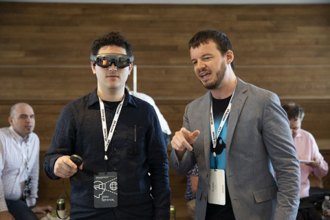 Man stands wearing a VR headset and using a hand-held controller, next to another man.