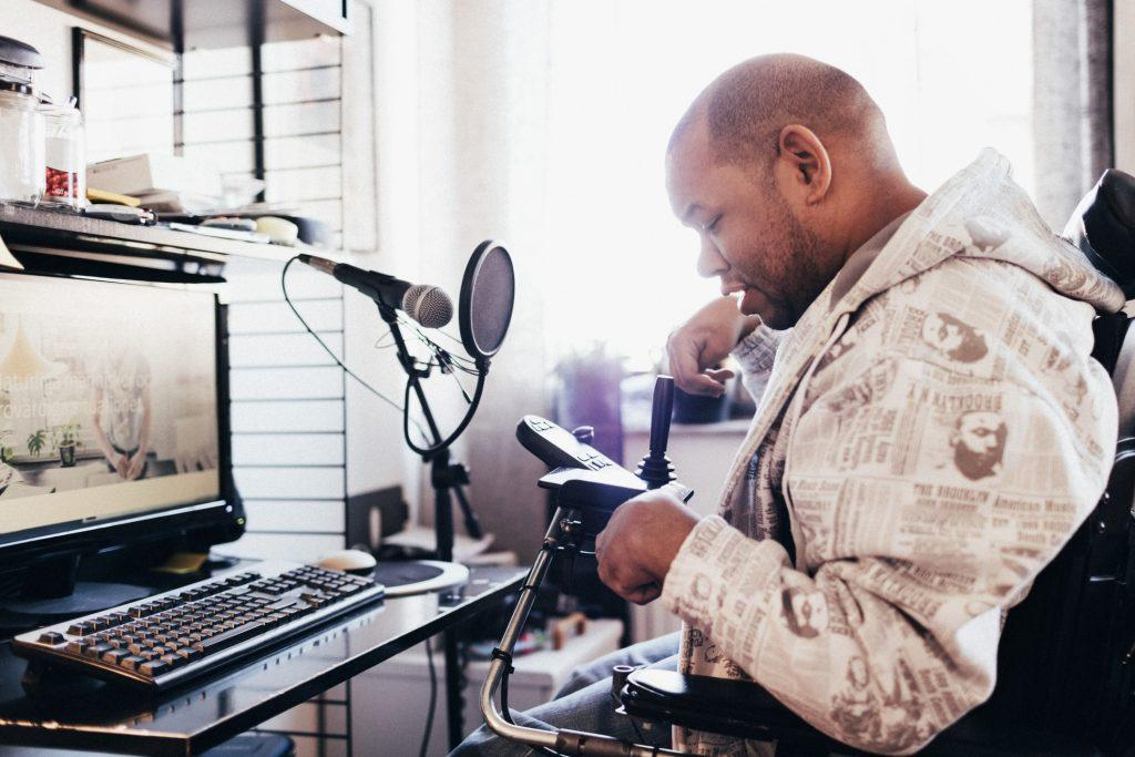 A black man using a power wheelchair recording a podcast on his computer.